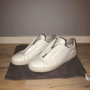 Vita Axel Arigato clean 90 zip sneakers storlek 46, använd ett fåtal gånger. Köpte dom på Axel Arigato butiken i Stockholm, nypris 1800kr