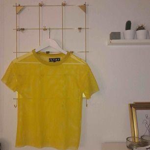 Gul tshirt i nät köpt på carlings! Använd vid två tillfällen så den är i toppenskick! Frakten bjuder jag på (: