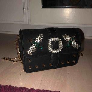 Cool handväska från Topshop med detaljer. Använd endast en gång så är så gott som ny! FRAKT INGÅR
