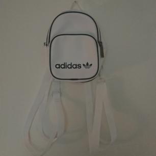 Helt ny oanvänd äkta Adidasväska i skinn. Vit med svarta detaljer två fack och flyttbara/avtagbara remmar så den kan bäras som cross body eller hur en vill!