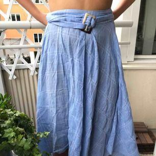 Ljusblå kjol med vita tunna rutor (se bild). Skärp till i midjan vilket gör att både en medium person och en XL person kan passa i kjolen. (Köper står för frakten)