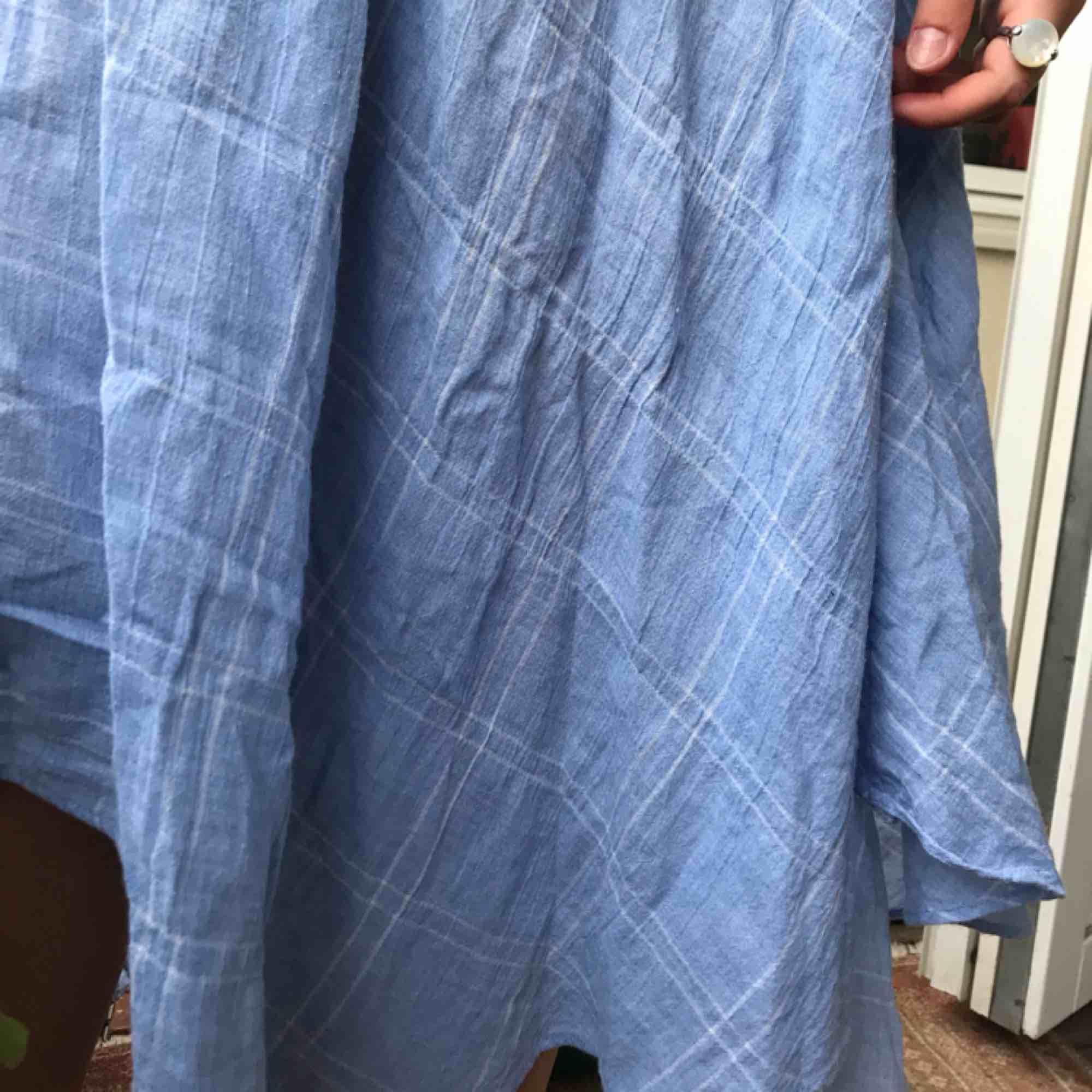 Ljusblå kjol med vita tunna rutor (se bild). Skärp till i midjan vilket gör att både en medium person och en XL person kan passa i kjolen. (Köper står för frakten). Kjolar.