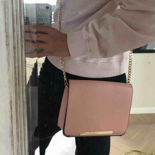 Fin rosa väska med guld detaljer! Mycket utrymme, har vikt in banden som ni ser på bilden och om man viker ut dom blir den ner till rumpan ungefär💓