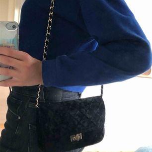Skit snygg väska med svart sammets tyg och guld detaljer, har vikt in banden och om man viker ut dom är väskan ner till rumpan ungefär💓
