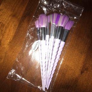 Unicorn Makeup Brushes från Basics har ett skaft i puderrosa, format som hornet på en enhörning, och borstar med vackra regnbågsfärger i pastell. De är helt nya och har inte använts!