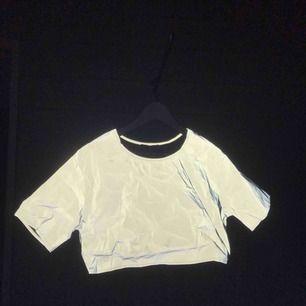 Splitterny croppad T-shirt i reflex. Jättesnygg men för liten för mig tyvärr. Köparen betalar frakt💛