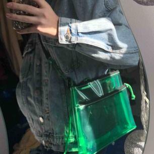 Grön transparent väska från bershka,kommer tyvärr aldrig till användning .justerbart band.litet fack i och en på utsidan .kan möta upp i Uppsala/Stockholm annars tillkommer frakt