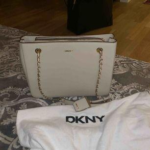 Säljer denna äkta DKNY-väska med gulddetaljer p.g.a. har alldeles för många väskor. Väskan är i väldigt fint skick, enbart använd vid två tillfällen. Ej prutbart pris. Möts upp i centrala Göteborg, annars får köparen stå för frakten (skickar spårbart).