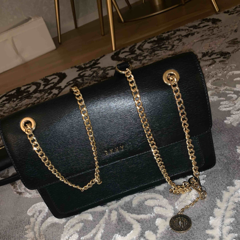 Svart, äkta DKNY-väska med gulddetaljer till salu. Väskan är i väldigt bra skick. Ej prutbart pris. Möts upp i centrala Göteborg, annars får köparen stå för frakten (skickar spårbart).. Väskor.