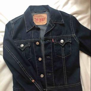 En Levis jeansjacka som är mörkblå med tydliga sömmar. I mycket bra skick och använd max 3 gånger. Är i storlek S men passar även en person i XS om man gillar något oversized. Eventuella fraktkostnader.