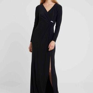 Vacker, oanvänd hellång svart klänning från Ralph Lauren! Köpt i början av sommaren, men tillfälle gavs aldrig att använda den. Strl 42 men är aningen mindre i strl! Glittrigt spänne i sidan, omlottmodell över bysten. Stilfull slits på vä sida.