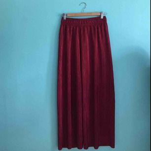 Vida plisserade byxor i storlek XS/S. Vinröda och glansiga. Knappt använda!