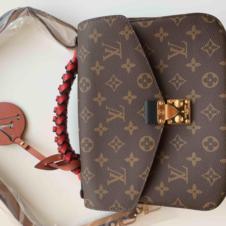 Ny väska inspirerad av LV metis Pochete  Väskan är  i äkta skinn.    Aa kopia Längd 24 cm, bredd 6 cm, höjd 18 cm. Oanvänd  hänger kan tas bort om Man inte vill ha den  Kan fraktas . Väskor.