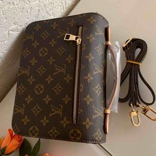 Ny väska inspirerad av LV metis Pochete  Väskan är  i äkta skinn.    Aa kopia Längd 24 cm, bredd 6 cm, höjd 18 cm. Oanvänd  hänger kan tas bort om Man inte vill ha den  Kan fraktas