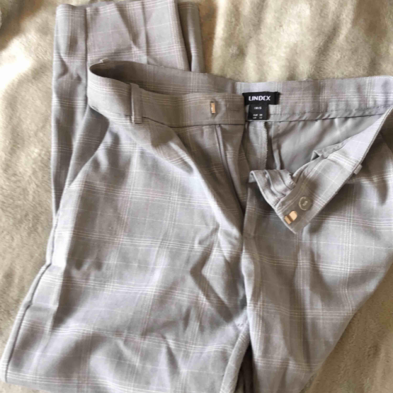 """Kostymbyxor från Lindex, modell """"iris"""". Medel midjelängd. Ljusgråa med vitt rutigt mönster. Säljer pga för korta i benen för min smak (173cm). . Jeans & Byxor."""