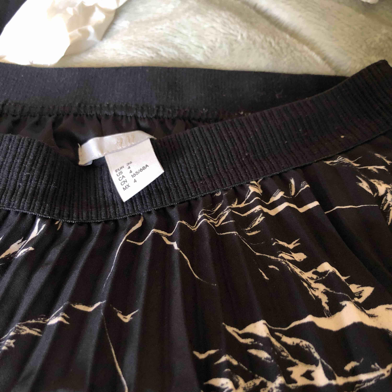 Veckad svart kjol med vitt mönster. Storlek 36. Från H&M. Endast använd 1 gång. Går lite över knät på mig som är 173. Passar även mindre storlekar då det är stretch i midjan. Frakt tillkommer på 36kr.. Kjolar.