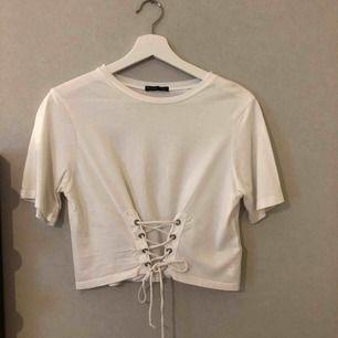 Vit t-shirt från Zara med en snygg snörnings detalj☺️ Använd 2 gånger, det går enkelt att justera hur hård/lös knytning man vill ha. Frifrakt🌟