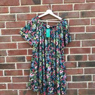 Helt oanvänd ny blommig klänning! Kan bäras off shoulder, prislappen är kvar