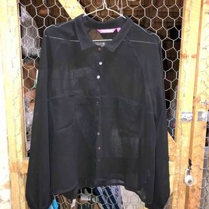 Genomskinlig svart blus med två fickor.