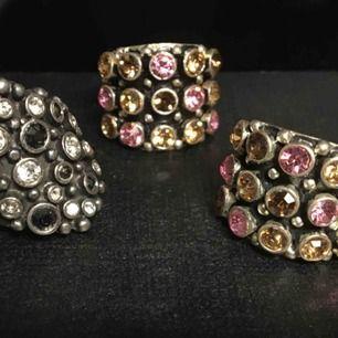 Breda ringar i stil med kumkum. Massa glittrande stenar. Ej äkta silver. Skickas för 18kr. 50kr/styck