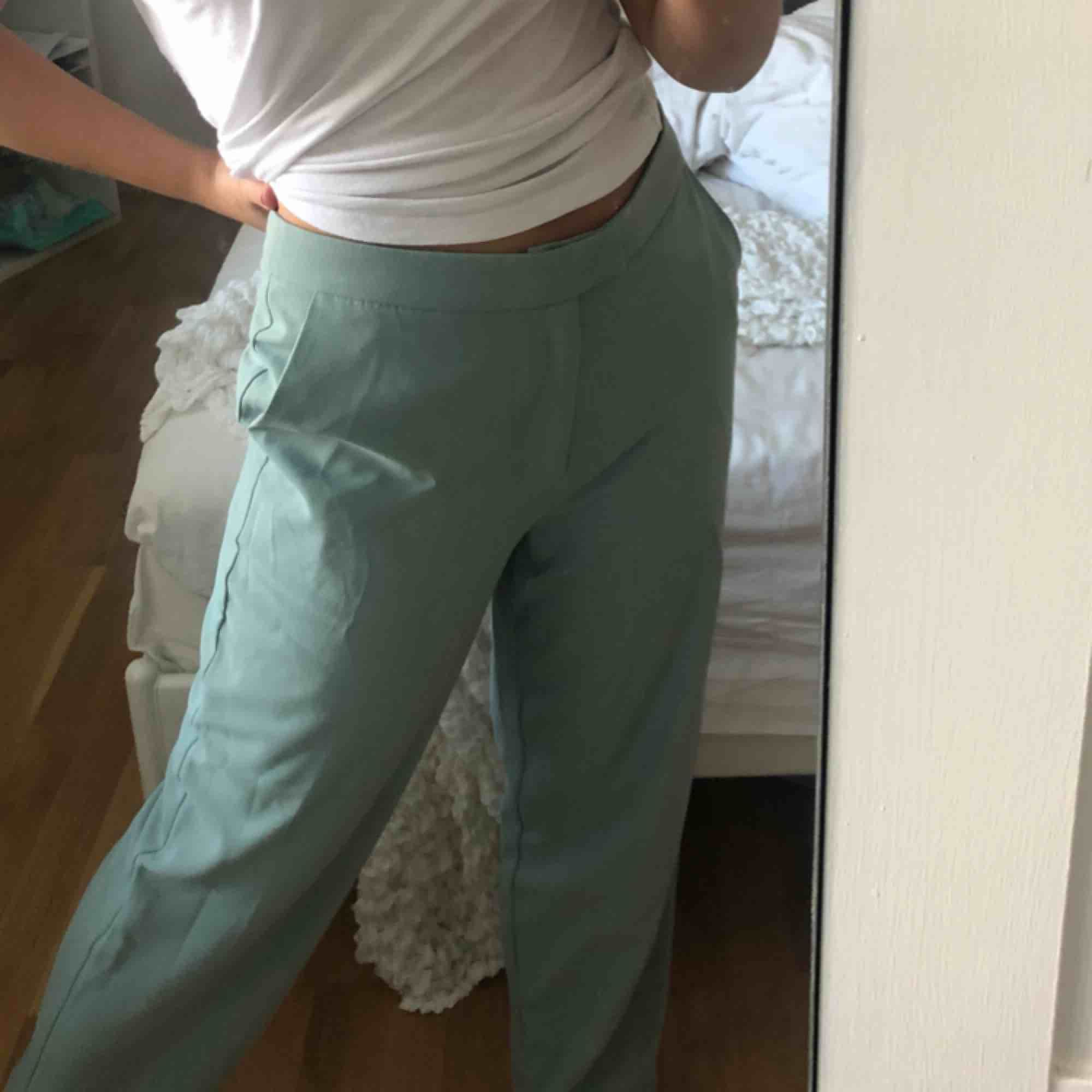 Mintgröna/ blåa flare byxor från NAKD i storlek S. Sjukt snygga till både vardags och fest. . Jeans & Byxor.