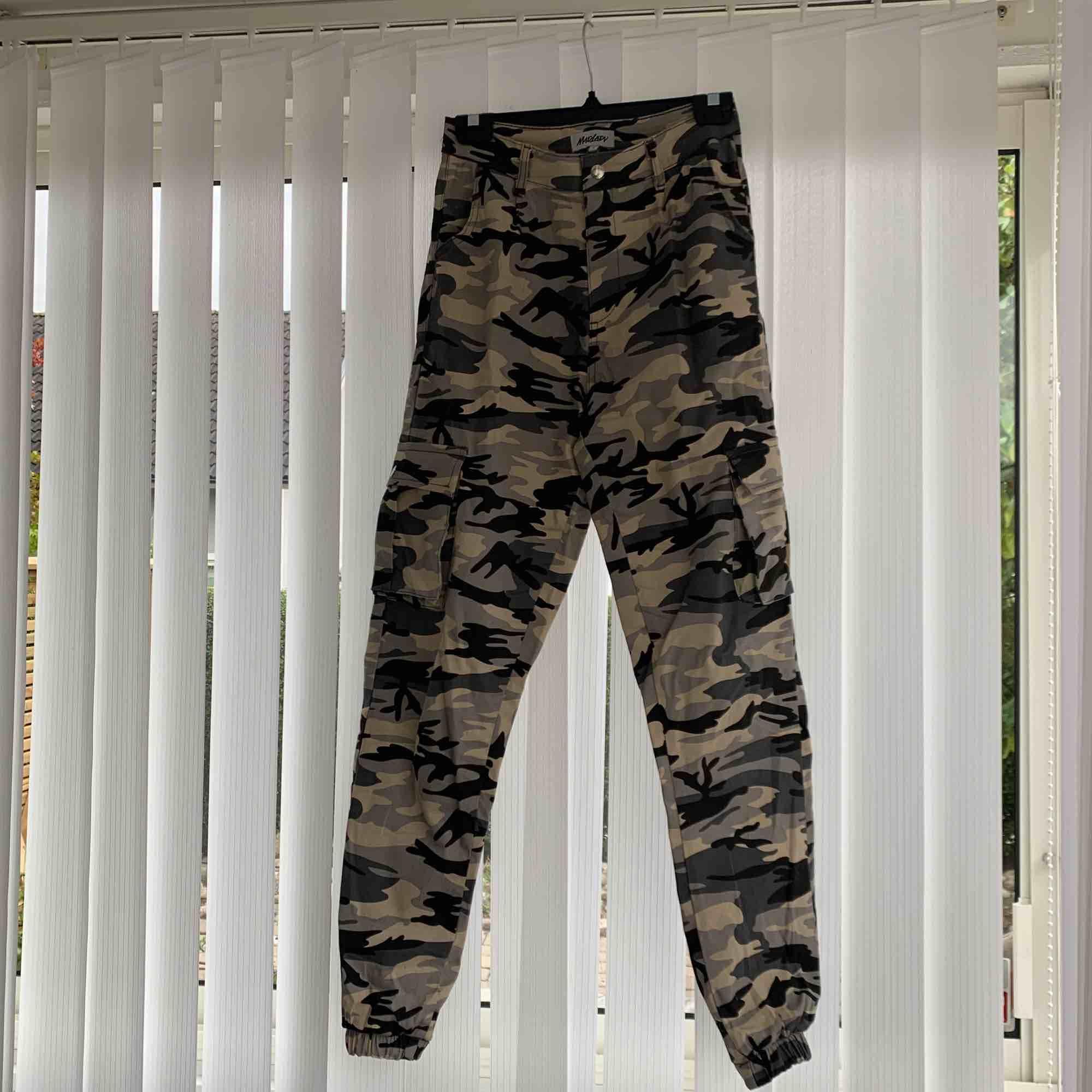 Beigea camo cargobyxor med bra passform och fickor på sidorna och muddar på byxbenen. Jeans & Byxor.
