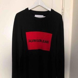 En svart stickad tröja ifrån Calvin Klein med röd logga  I bra skick, använd en gång  Inköpt för ca 800kr