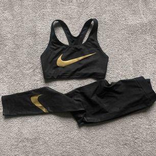 Nikes stilsäkert gym-set, leggings + sport-bh med bra stöd. Storlek S i båda. Nike loggan är lite skadad på benet men loggan är bak på vaden och längre ner så inget man ser eller tänker på ✨ Färgen guld svart. Säljer dessa ihop, frakt tillkommer på 72kr