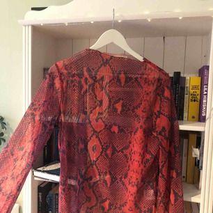 Snygg mesh-tröja från Junkyard i ormskinnsmönster, skitsnygg att ha under en vanlig vit/svart t-shirt! Ärmen är bredare nertill och har slits(se andra bilden). I strl L men passar även M bra. Köparen står för frakten!