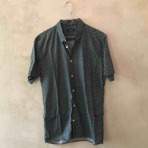 Kortärmad skjorta i grönt och svart rutmönster.