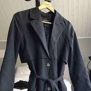 Mörkgrå kappa från Monki, i bra skick, bälte i midjan, fickor, finns fortfarande i butik för 600:-
