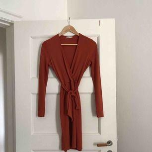 Ribbad klänning från Nelly trend med band i midjan. Använd en gång.