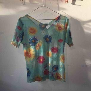 Genomskinlig, ljusblå mesh-tröja med blommor och vågig kant