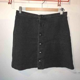 Jeanskjol i mörkgrå jeans, knappar hela vägen. Storlek L/40