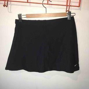 Sportig Nike-kjol i svart, lite slits i sidan. Shorts i kjolen men går att klippa bort