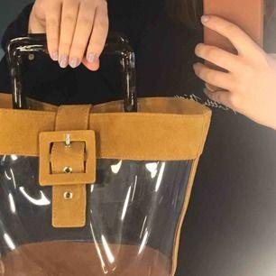 Så fin, genomskinlig väska med mockadetaljer! Rymlig och kommer med längre band. Aldrig använd:)