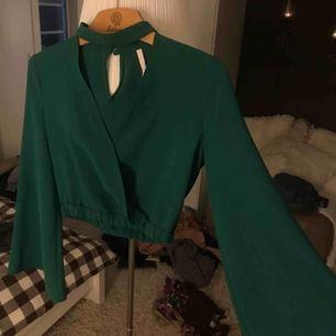 Zara grön topp med djup urringning och trumpetärmar. Croppad.