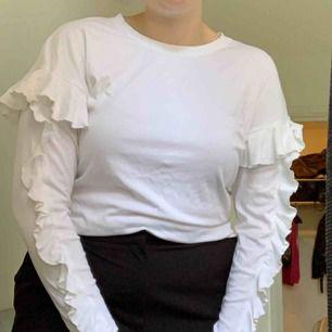 Fin mjuk vit basic långärmad tröja med volang ärmar o även volang baktill. Väldig stretching i materialet vilket är skönt, använd fåtal gånger.