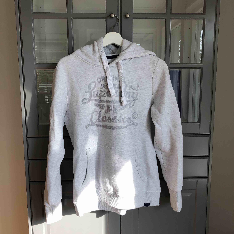 Säljer min SuperDry hoodie i grå/vit. Köpt för 399kr. Den är oversized och väldigt mysig att ha på sig! köparen står för fraktkostander :). Huvtröjor & Träningströjor.