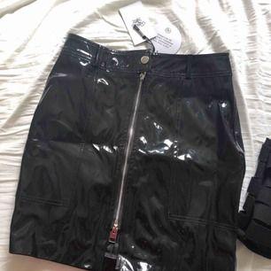 Oanvänd svart lackkjol från Rebecca Stella med lapparna kvar!