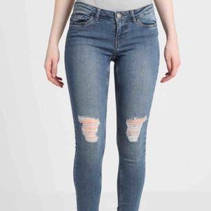 Ett par blåa jeans med slitningar från Noisy May. Köptes för ungefär ett år sedan, men är inte använda jättemycket. Det är isåfall hålen på knäna som töjts ut lite.  Köparen står för frakten. Ursprungspris: 350kr
