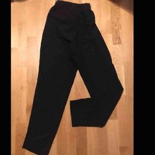 Högmidjade svarta kostymbyxor med knut i midjan. Tunna och sköna byxor från Monki i bra kvalité.