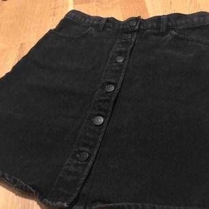 Svart jeanskjol med knappar framtill. Fickor på baksidan och framsidan. Från Monki