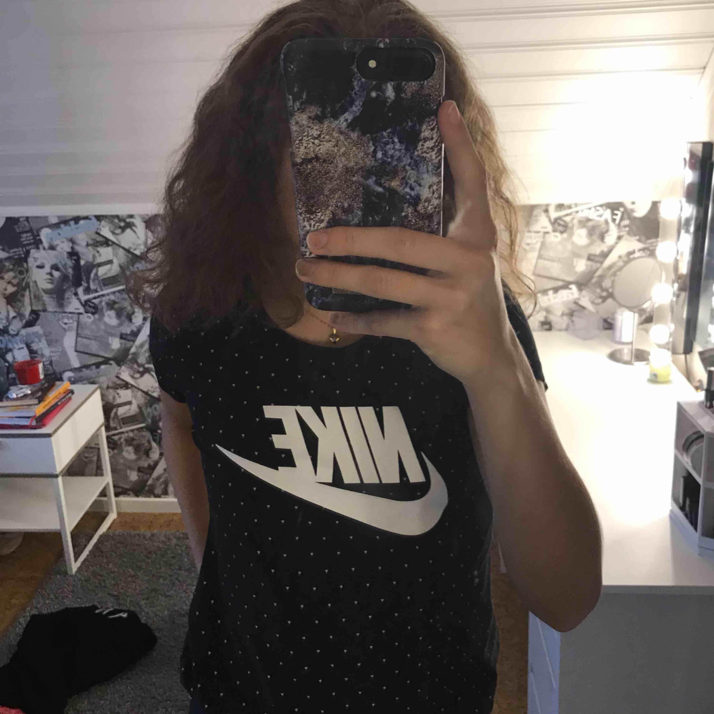 En svart tröja med vita detaljer från Nike, säljer den för att de är lite stor för mig. T-shirts.