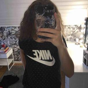 En svart tröja med vita detaljer från Nike, säljer den för att de är lite stor för mig