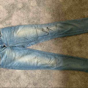 Lågmidjade blåa jeans med slitningar på ena knät. Säljer pga för småa!
