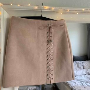 Puder-rosa kjol i typ fake-mocka material från BikBok. Använd Max 3 ggr och i nyskick. Säljer pga använder aldrig! Köpare står för frakt.