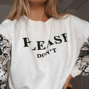 """Tröja med texten """"please don't"""" på framsidan och ärmar med ormskinnsmönster. Sparsamt använd. Dock med en liten fläck på framsidan som inte gått bort. Syns dock knappt."""