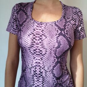 T shirt i ormskinnsmönster i polyester.  Stl XS-S men kan nog även passa en M eftersom den är i stretch.           Köpare betalar frakt /kan mötas upp i Sthlm.