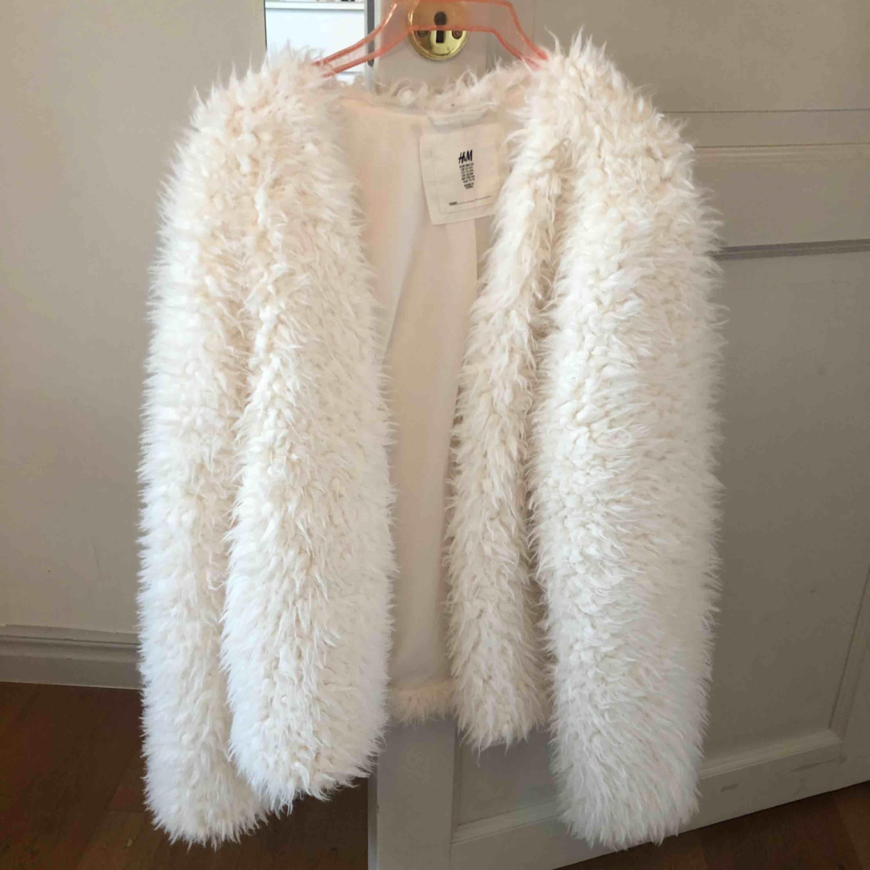 Helt oanvänd fluffig vit jacka/kofta från H&M. Köpt för 499kr. Frakt ingår. Jättebra skick i med att den aldrig är använd, säljer den pga att jag inte kommer använda den!. Jackor.
